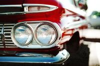 A close up of a classic red car's right headlight, blinker, and bumper, and the perspective of the right side of the vehicle with chrome details
